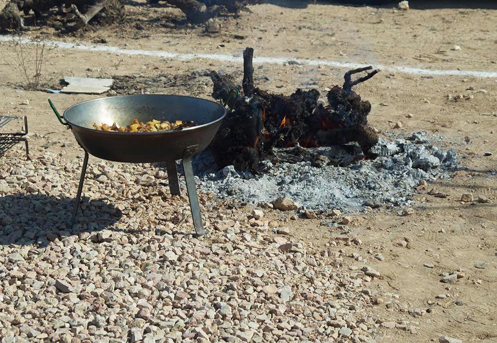 Sartén de tres patas al lado de una pequeña hoguera con migas manchegas cocinadas al fuego