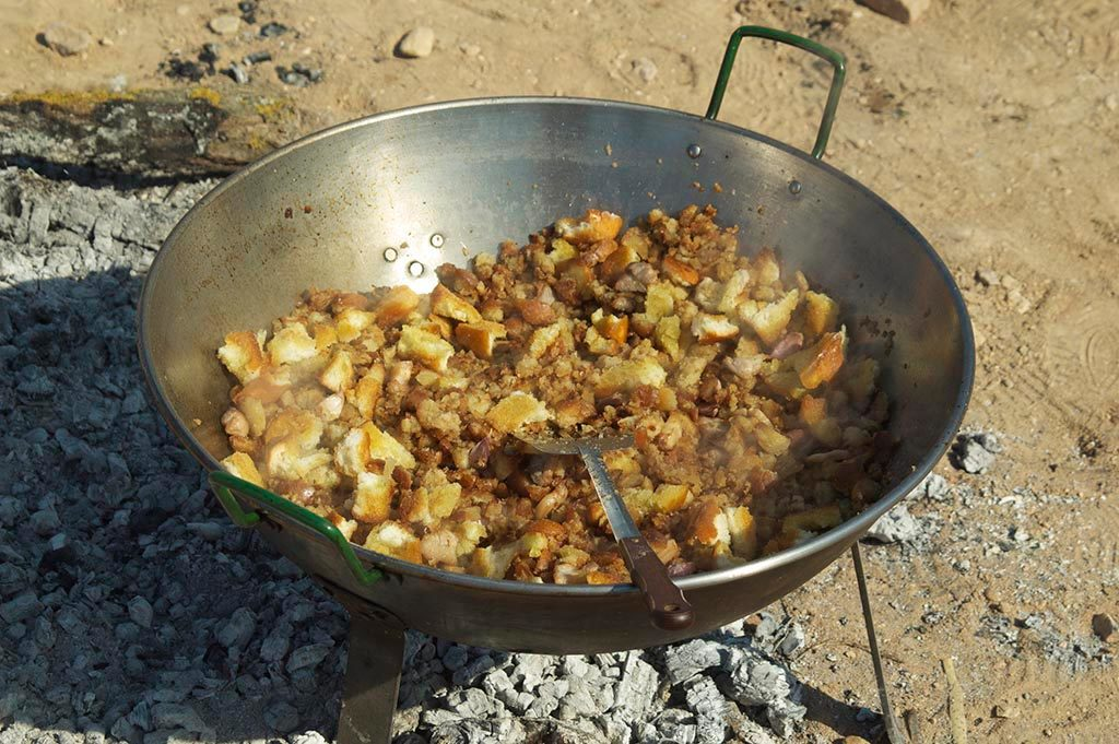 Poêle avec migas manchegas cuisinées au feu